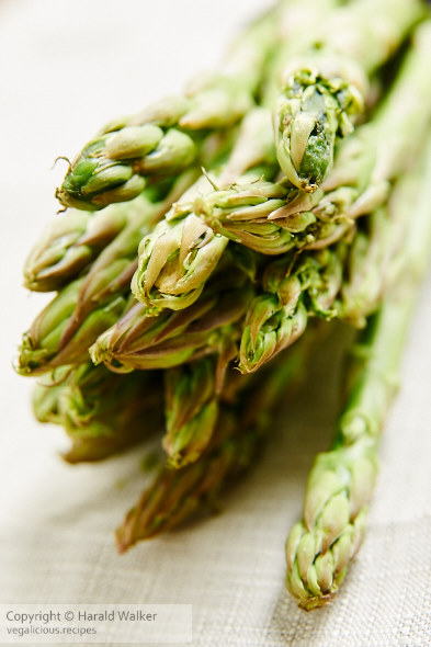 Bundle of fresh green asparagus on a white table cloth.