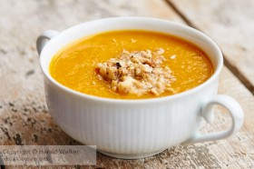 Soup bowl with a pumpkin and mango soup, garnished with chopped walnuts.