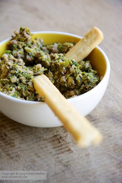 Kale and walnut pesto in small bowl with breadsticks (grissini).